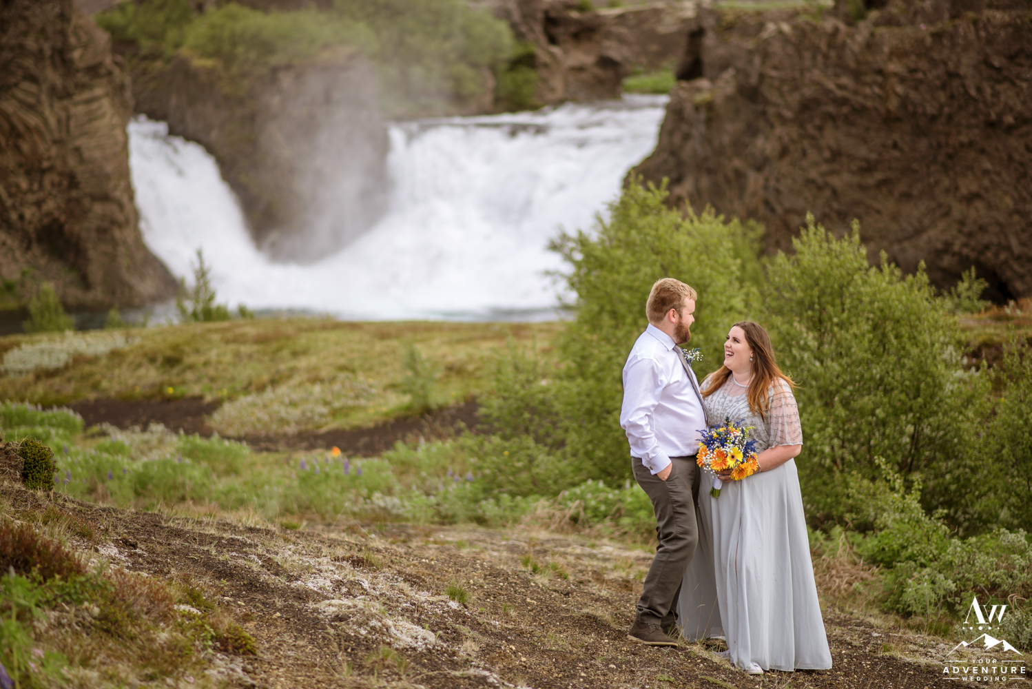 Iceland Wedding Couple looking at each other at Hjalparfoss Waterfall