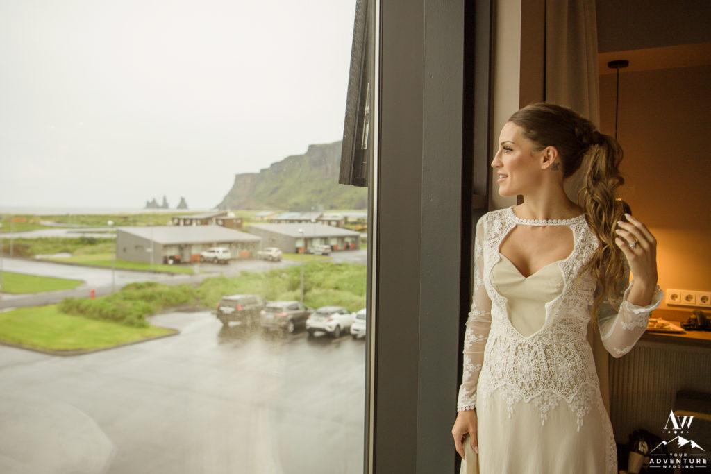 Bride looking out of window at Icelandair Vik