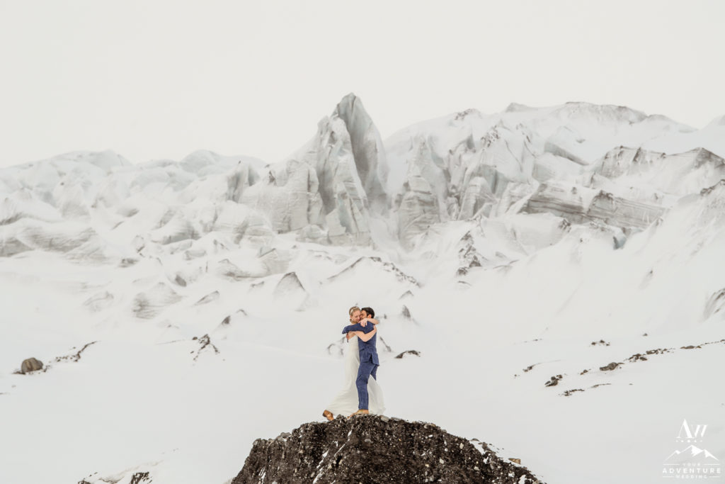 Iceland March Wedding Couple hugging in front of a glacier