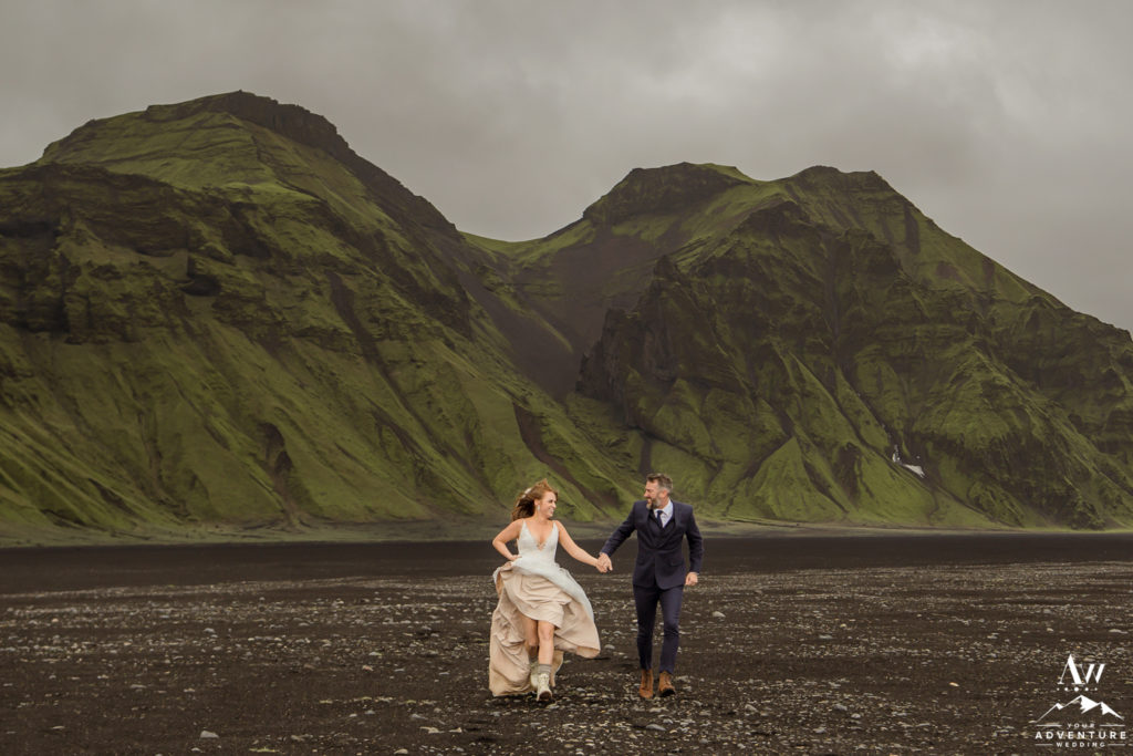 Couple running during wild wedding adventure in Iceland