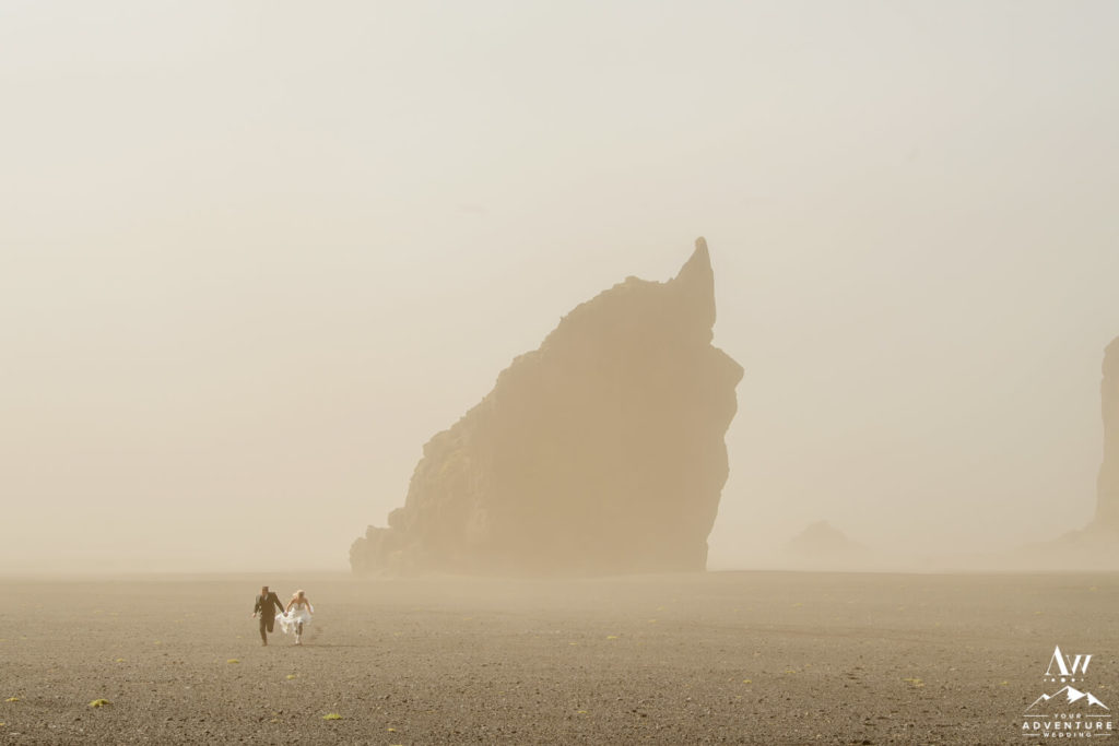 Weather in Iceland Couple running in a sand storm