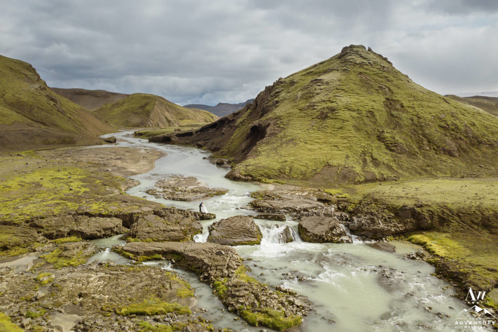 Iceland Summer Nuptials Couple standing on top of a waterfall