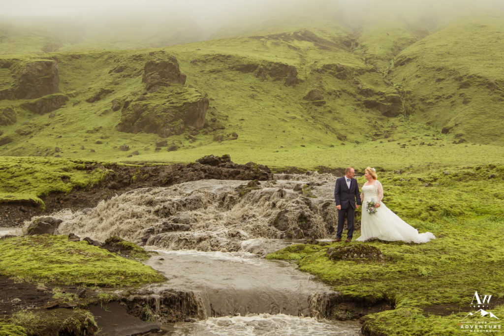 Iceland wedding couple next to glacier waterfall