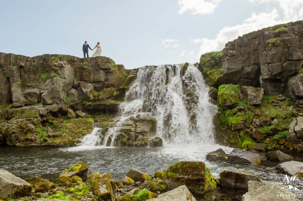 Iceland Wedding Couple standing on top of a waterfall