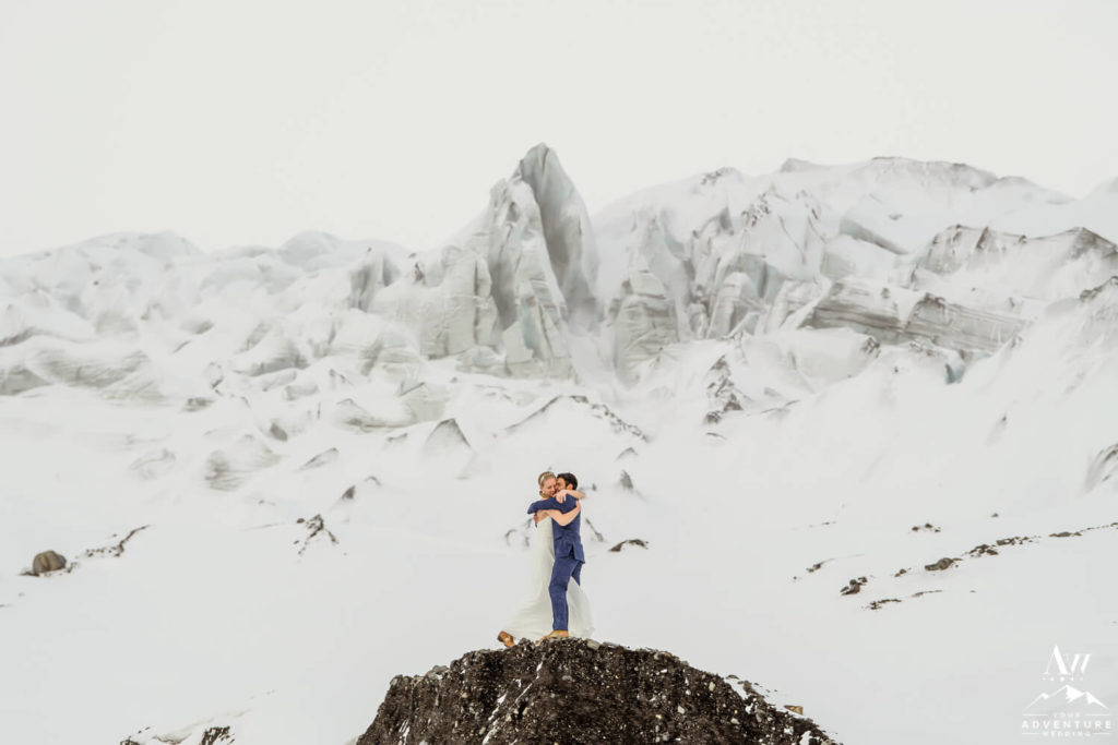 Iceland wedding couple hugging in front of a glacier ice fall