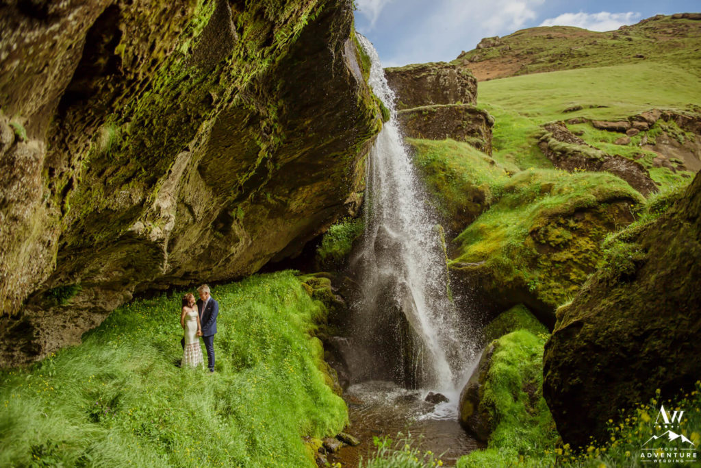Iceland wedding couple standing behind a waterfall