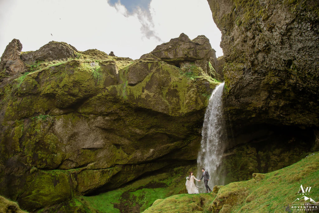 Elopement couple walking in front of a waterfall