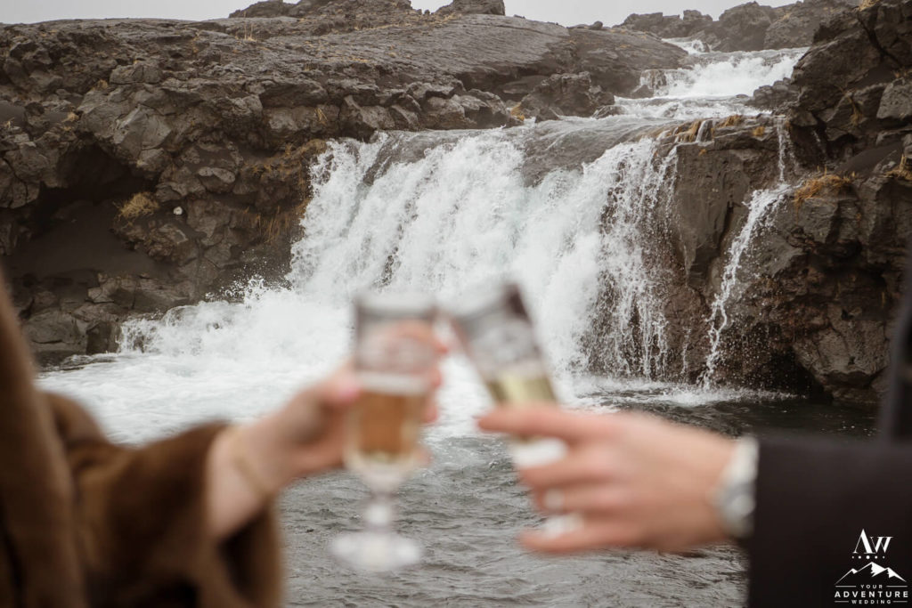 Iceland elopement couple toasting champagne in front of a waterfall