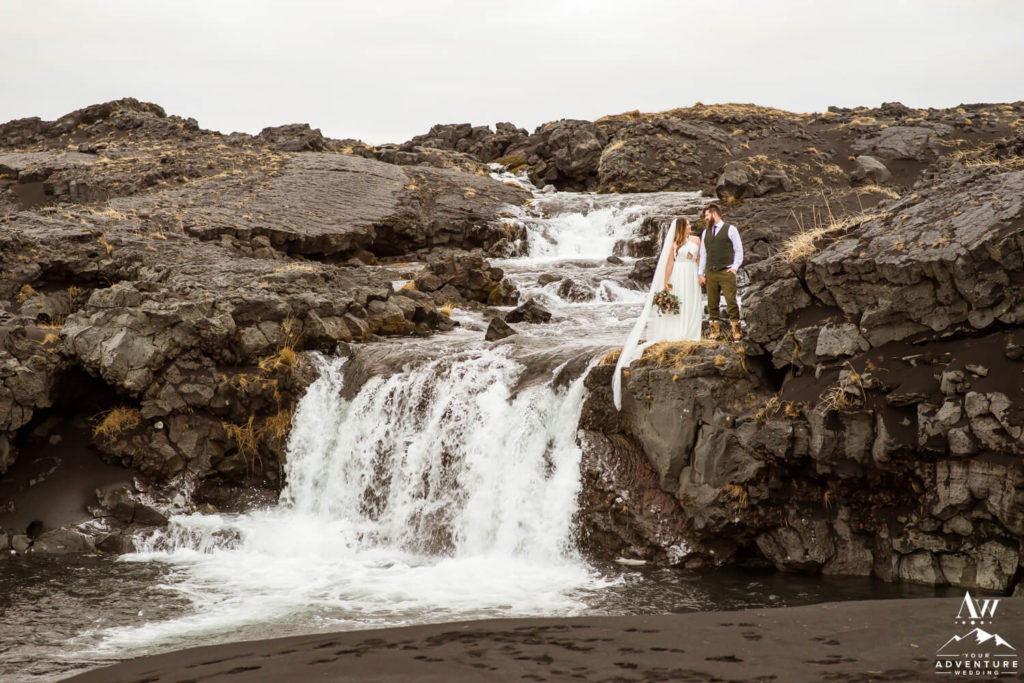 Iceland wedding couple at black beach waterfall