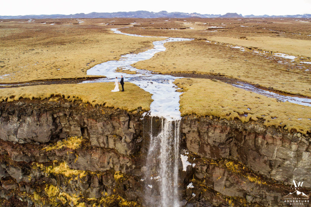 Winter Iceland Wedding Couple on top of a waterfall