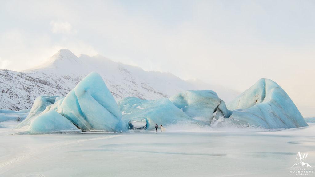 Frozen Lake Elopement Couple Walking in front of iceberg