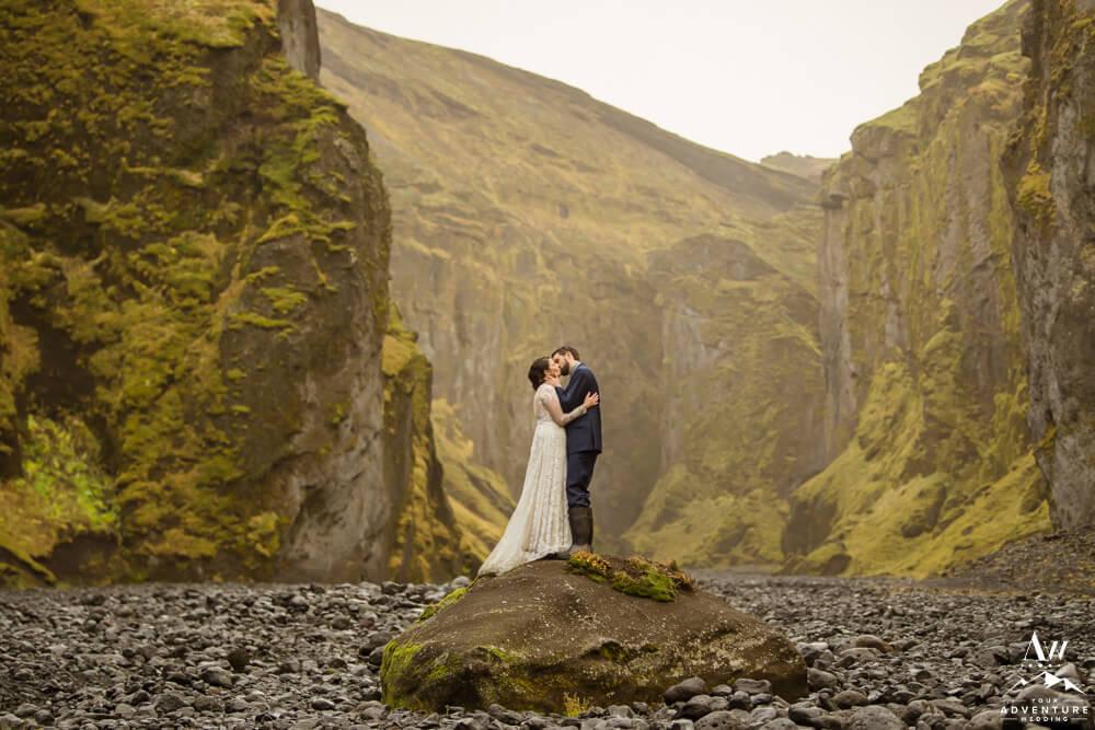 Couple kissing inside Stakkholtsgjá Canyon